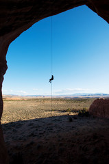 Silhouette woman rappelling against sky on sunny day