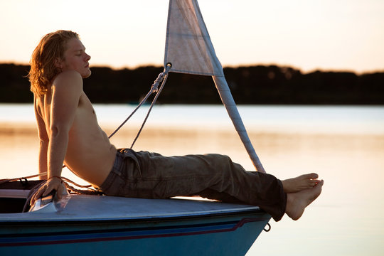Man relaxing while sitting on sailboat