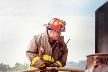 Firefighter holding fire hose against sky