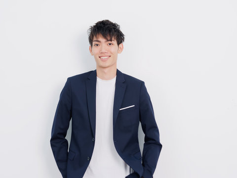 Portrait of handsome Chinese young man in dark blue leisure suit posing against white wall background. Hands in pocket and smiling at camera, looks confident.