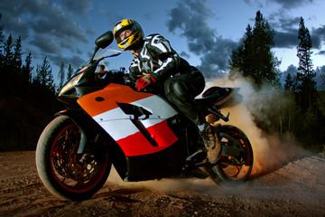Man riding motorbike against sky at dusk