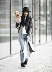 A girl walks with a dog after shopping