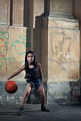 Portrait of girl playing basket ball against wall