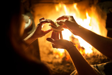 Cropped image of couple holding smores while sitting near to campfire at night