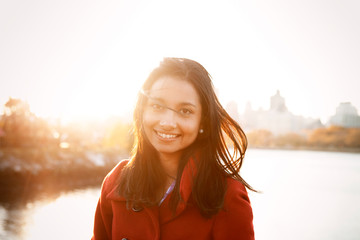 Portrait of happy young woman against lake during sunset