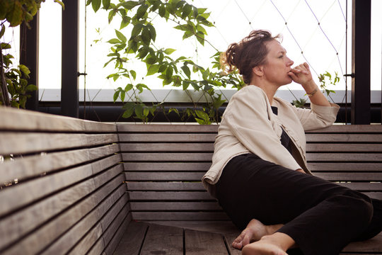 Thoughtful woman looking away while sitting on bench at park