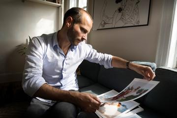 Man looking at photographs while sitting on sofa at home