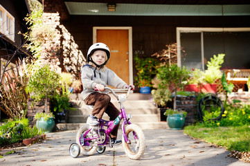 Portrait of boy with bicycle against house