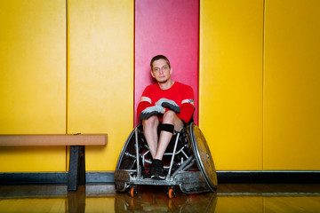 Portrait of adaptive athlete sitting on wheelchair against wall