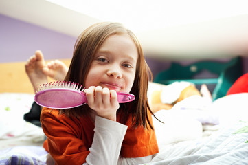 Portrait of girl holding hairbrush while lying on bed at home