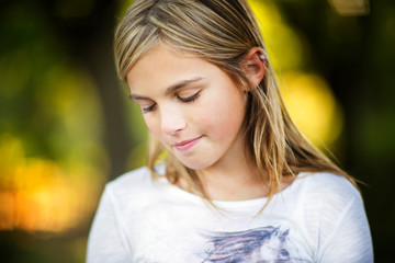 Girl looking down while standing at park