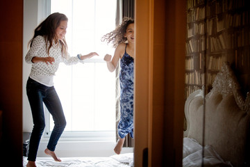 Playful sisters jumping on bed at home