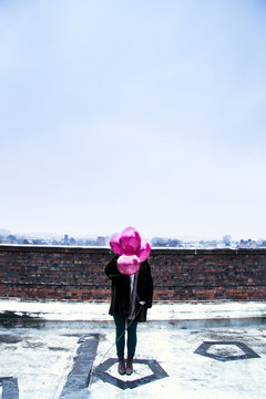 Woman covering face with pink balloons while standing on building terrace against sky