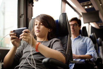Boy listening music on mobile phone while passengers sitting in bus