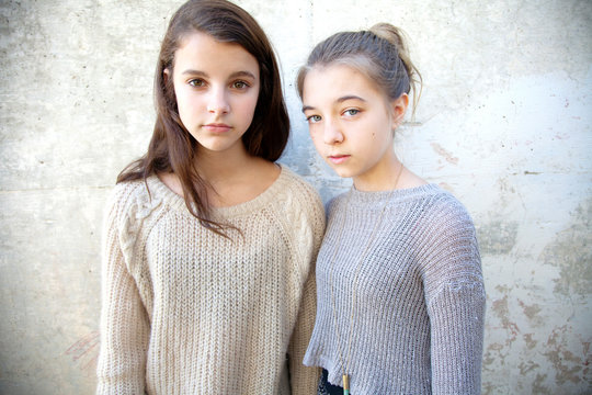 Portrait of sisters wearing sweater standing against wall
