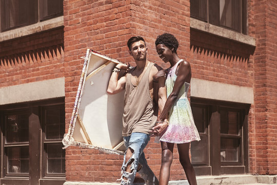 Artist carrying canvas while walking with woman in city