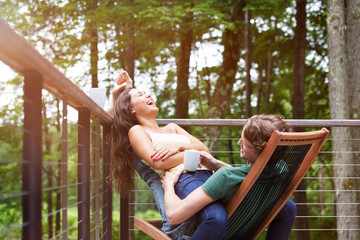 Couple laughing while sitting on chair by railing