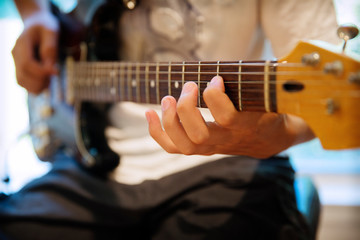 Midsection of teenager practicing electric guitar at home