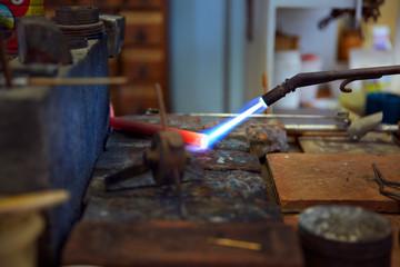 Welding torch heating metal in workshop