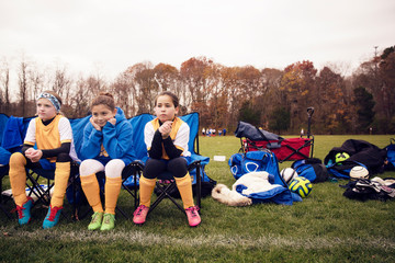 Soccer players sitting by sports equipment on playing field