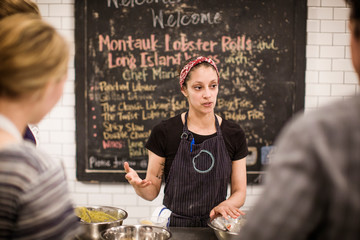 Female chef explaining recipe while standing against blackboard at commercial kitchen