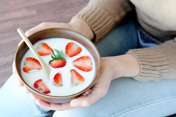 Hand of woman holding bowl of fresh strawberry and yogurt .Concept of healthy diet and weight control