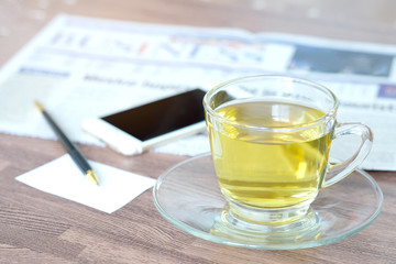 Cup of green tea hot on the desk has a newspaper and a tablet. at office