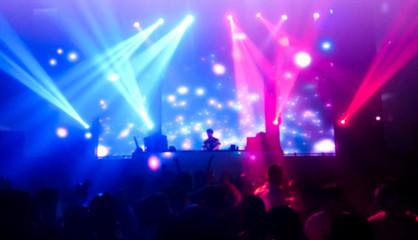 DJ turns music people dancing in night club with beautiful light, women and men in the happy fun.photo blur