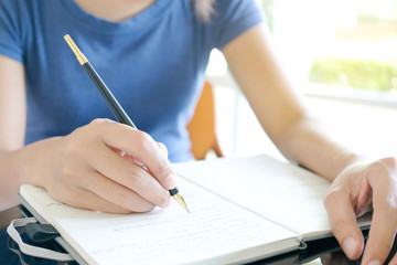 Woman's hand Writing in the notebook In the living room, the concept of education and work.