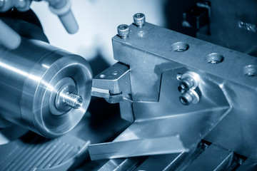 The CNC lathe or turning machine cutting the thread  at the metal  shaft.Hi-technology manufacturing process.