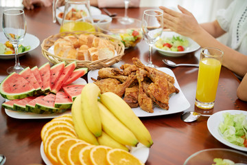 Delicious deep fried chicken and fruits on dinner table