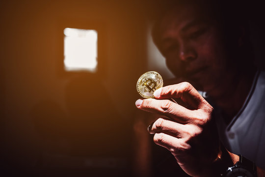 Business concept image; Man holding in hand symbol of crypto currency ;Cryptocurrency golden bitcoin