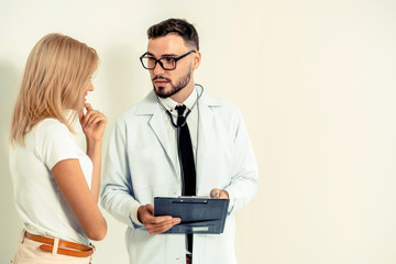 Male doctor and female patient with documents of patients health record are having conversation in hospital. Healthcare and medical service.