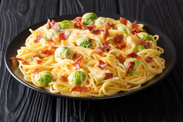 Spicy spaghetti cooked with Brussels sprouts, bacon, garlic with melted creamy cheese close-up on a plate. horizontal