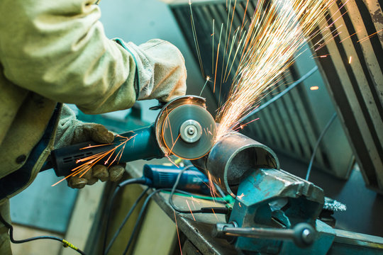 mechanic cleans a welded seam on a section of a steel pipe with the help of a grinding machine in the metal workshop