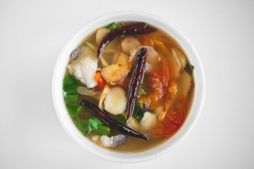 Top view of hot and spicy Thai Tom yum kung with ingredients and herbs.