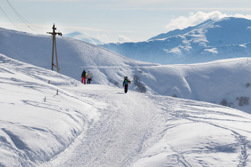 Fototapeta Skiers and snowboarders go on snow road