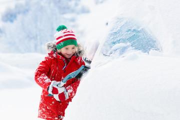 Child brushing off car. Kid with winter snow brush