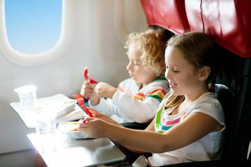 Child in airplane. Kids fly. Children flight meal