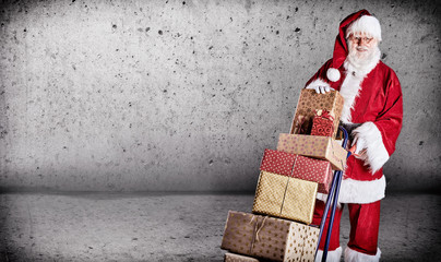 Father Christmas pushing a trolley of Xmas gifts