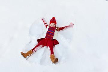Child making snow angel. Kids winter outdoor fun.