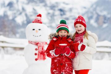 Child building snowman. Kids build snow man.