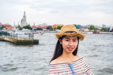 Asian woman tourist wear hat standing smiling with the background is a view of chao phraya river and pagoda arun temple landmark and attractions of Bangkok Thailand.
