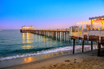 Scenic coastal landscape illuminated by night of Malibu Pier in Malibu, California, United States see from Carbon Beach. Malibu Pier is an historic landmark. Blue hour shot. Copy space.