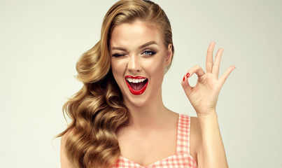 Pin-up retro girl with curly hair  winking, smiling and showing OK sign . Presenting your product....