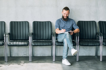 man sitting in the row of chairs writing. interview or job application concept.