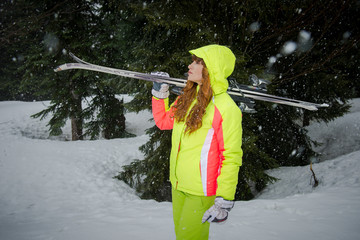 Girl in bright sportswear with skis. Woman skier. Active sports and recreation in the winter. Woman Skier carries skis on shoulder