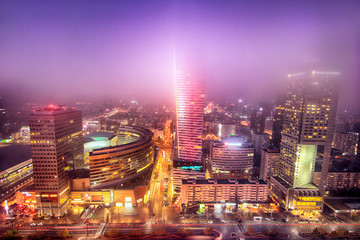 WARSAW, POLAND - NOVEMBER 4, 2018: Modern skyscrapers in the downtown district of Warsaw, Poland. Aerial view during the foggy night.