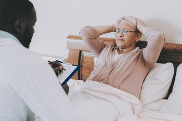 Doctor Fills Form. Man Examines Elderly Patient.