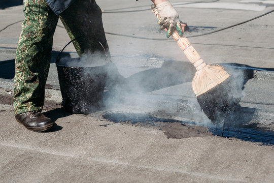 Worker repairs the roof with molten tar from a bucket with a broom.